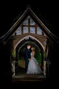 bride and groom under archway at night