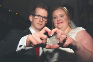 bride and groom making hearts with fingers