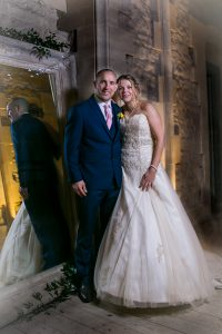 bride and groom by mirror at woodchester mansion wedding photographer