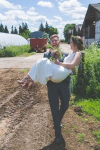 groom carrying bride over muddy field