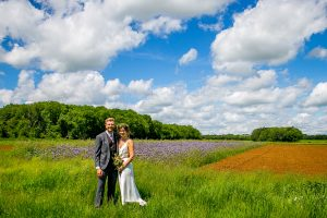 bride and groom in field with blue sky