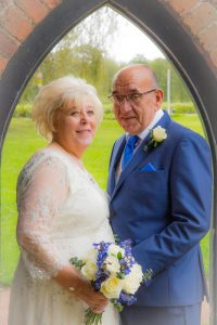 bride and groom in archway at stonehouse court