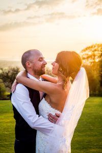 bride and groom with sun in background