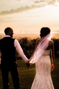 bride and groom looking into sunset
